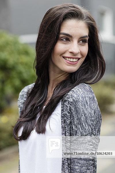 Porträt einer lächelnden jungen Frau mit langen braunen Haaren