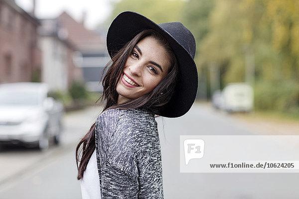 Porträt einer lächelnden jungen Frau mit schwarzem Hut über die Schulter schauend
