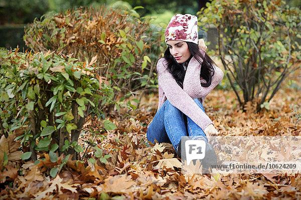 Junge Frau in Herbstmode auf dem mit Herbstblättern bedeckten Boden sitzend