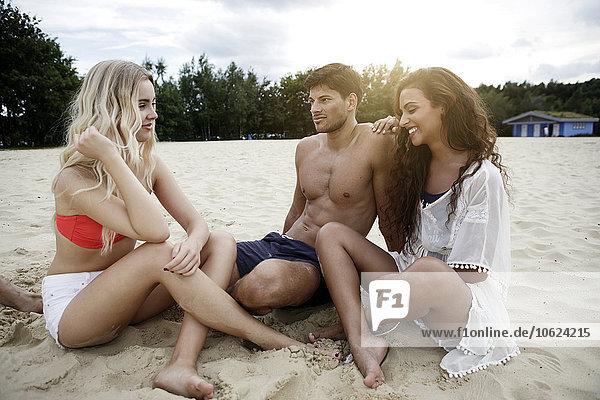 Deutschland  Haltern  drei Freunde am Strand sitzend