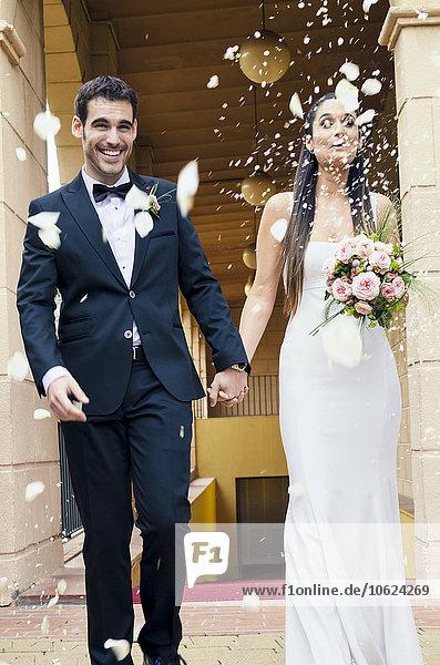 Brautpaar nach der Hochzeit bei Regen von Rosenblättern und Reiskörnern