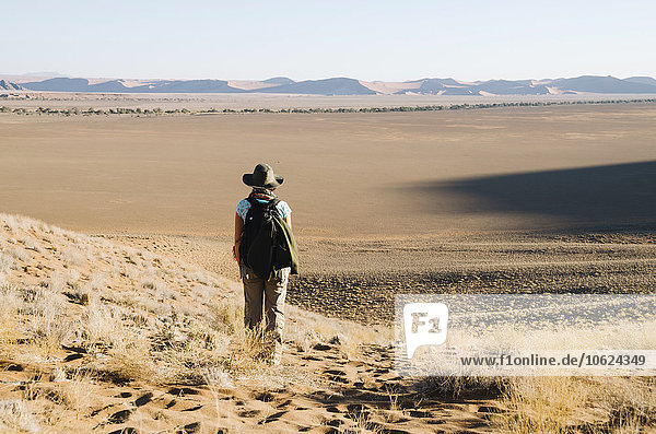 Namibia  Namib Desert  Sossusvlei  Woman with hat and backpack looking at the horizon