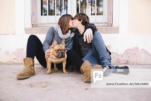 Junges Paar mit französischer Bulldogge auf dem Boden sitzend und küssend