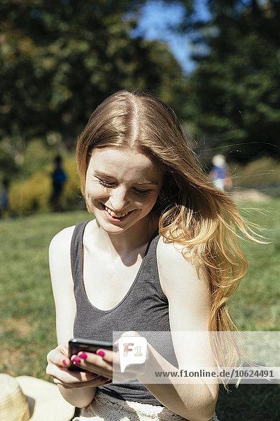 Junge Frau beim Telefonieren im Park