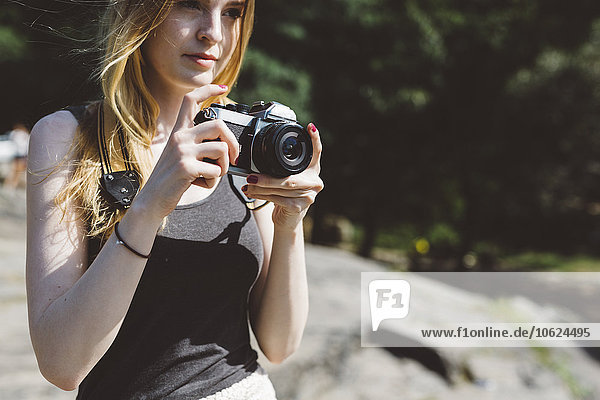 Young woman outdoors with camera