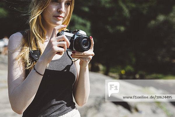 Junge Frau im Freien mit Kamera