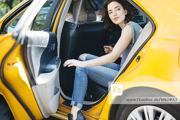 USA  New York City  portrait of young woman getting on a yellow cab