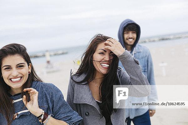 Italien  Rimini  Portrait von drei glücklichen Freunden am Strand außerhalb der Saison