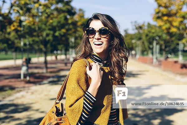 Stilvolle Frau im Park an einem sonnigen Herbsttag