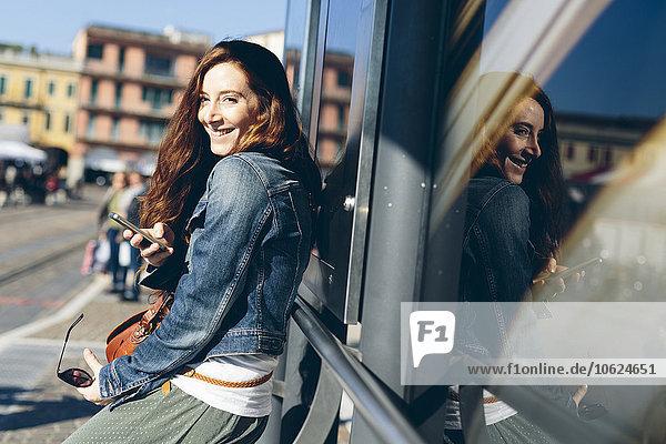 Italien  Padua  Frau an der Bushaltestelle mit Handy