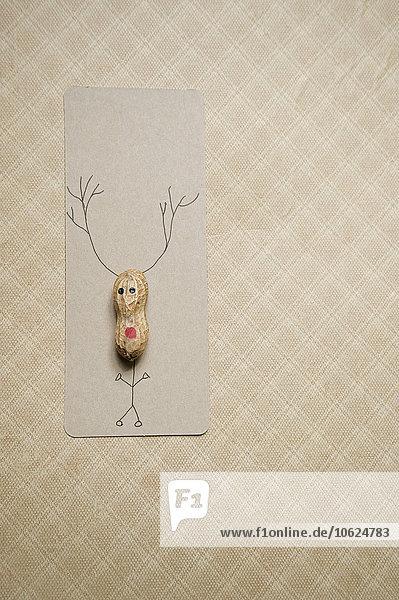 Selbstgemachte Weihnachtskarte mit Erdnuss in Rentierform