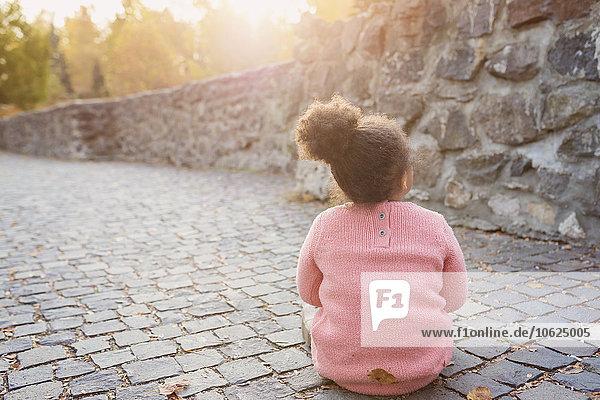 Kleines Mädchen auf dem Gehweg sitzend Kleines Mädchen auf dem Gehweg sitzend