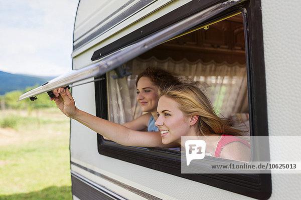 Zwei Freundinnen schauen durch das Fenster des Wohnwagens