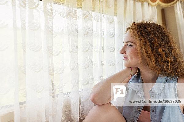 Lächelnde junge Frau sitzt in einem Wohnwagen und schaut durchs Fenster.