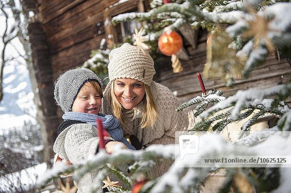 Österreich  Altenmarkt-Zauchensee  Mutter und Sohn beim Anblick des geschmückten Weihnachtsbaums vor dem Bauernhaus