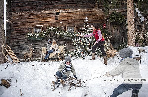 Österreich  Altenmarkt-Zauchensee  Familie vor dem Bauernhaus zur Weihnachtszeit