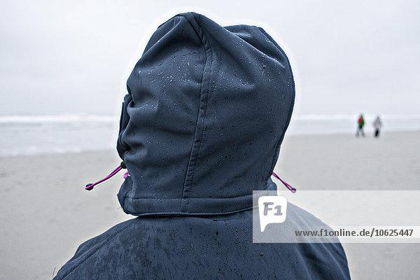 Deutschland  Insel Langeoog  Person mit nasser Haube am Strand