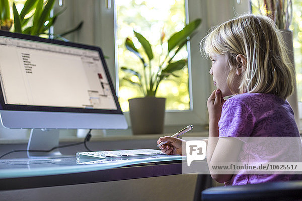 Little girl looking at computer monitor at home