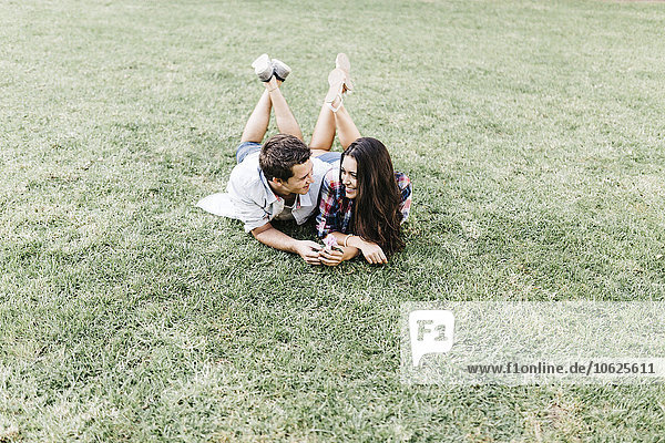 Young couple in love lying on a meadow in a park looking at each other