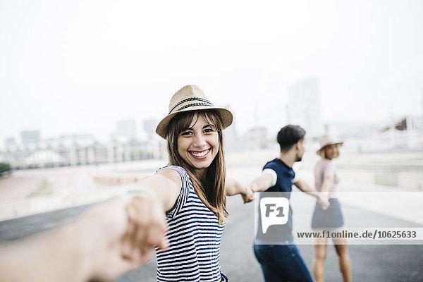Spanien  Barcelona  Porträt einer lächelnden jungen Frau  die mit ihren Freunden Händchen hält.