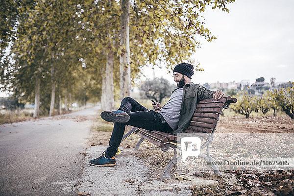 Spanien  Tarragona  junger Mann auf einer Bank an der herbstlichen Landstraße mit Blick auf sein Smartphone