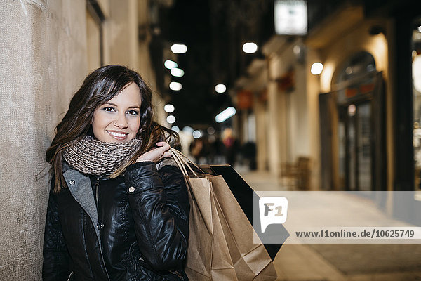 Spain  Reus  portrait of smiling young woman with shopping bags leaning at house facade at night