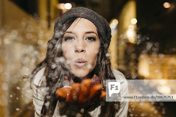 Spanien  Reus  Porträt einer jungen Frau  die nachts Schnee in die Luft bläst.