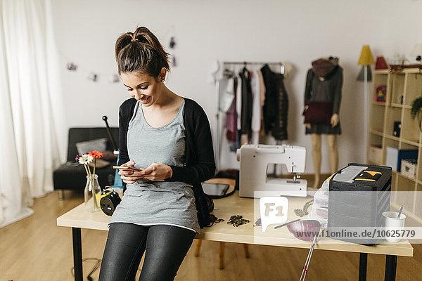 Junge Modedesignerin  die in ihrem Atelier mit dem Smartphone arbeitet.