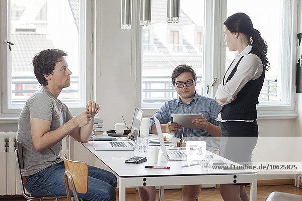 Drei kreative Geschäftsleute bei einem Meeting in einem modernen Büro