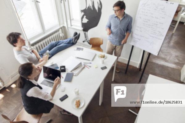 Verschwommener Blick auf drei kreative Geschäftsleute bei einem Meeting in einem modernen Büro