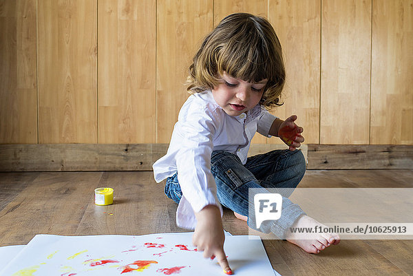 Little boy sitting on wooden floor painting with finger colours