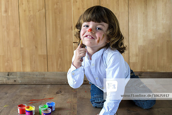 Portrait of little boy painting his face with finger colours