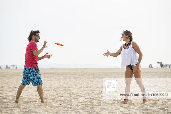 Spanien  Cadiz  El Puerto de Santa Maria  Paar beim Frisbee spielen am Strand