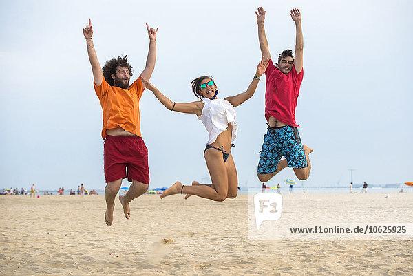 Spanien  Cadiz  El Puerto de Santa Maria  Freunde beim Springen am Strand