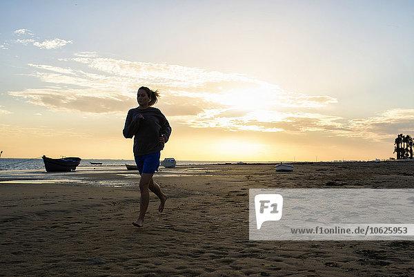 Spanien  Puerto Real  Frau beim Joggen am Strand bei Sonnenuntergang