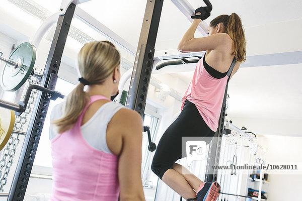 Frau beobachtet Athletin bei Klimmzügen im Fitnessstudio
