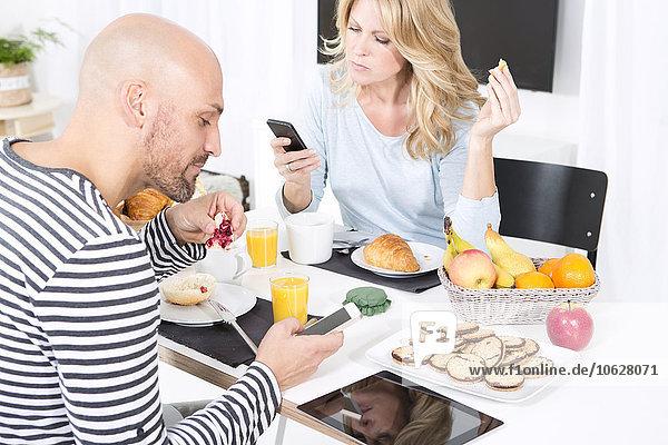 Paar am Frühstückstisch mit Smartphones