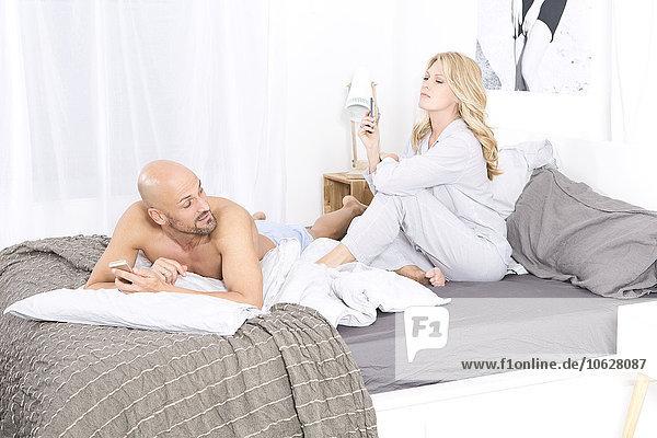 Reife Paare im Schlafzimmer mit ihren Handys