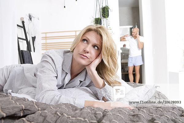 Verärgerte Frau liegt auf dem Bett  während der Mann im Hintergrund telefoniert.
