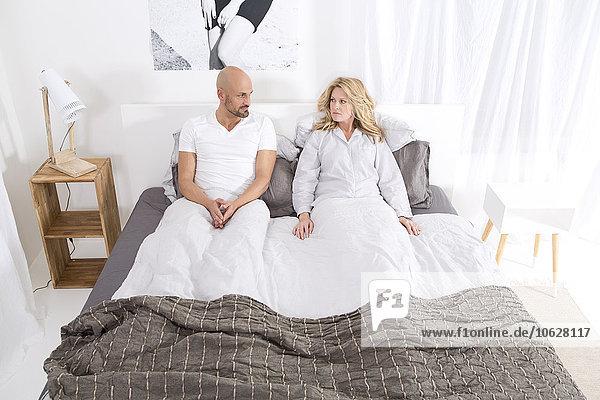 Ein reifes Paar  das im Bett liegt und Beziehungsprobleme hat.