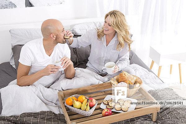 Glückliches Paar beim Frühstück im Bett