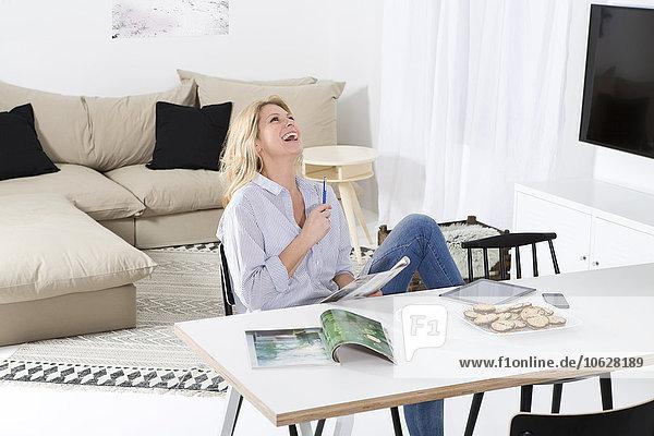 Lachende Frau sitzt am Tisch in ihrem Wohnzimmer mit Magazin