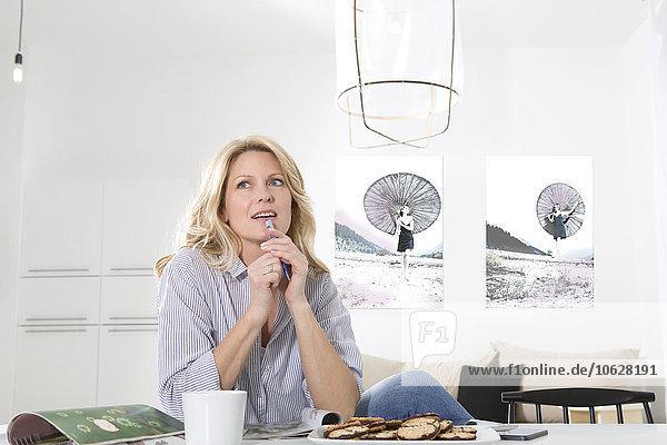 Frau sitzt am Tisch in ihrem Wohnzimmer und denkt.