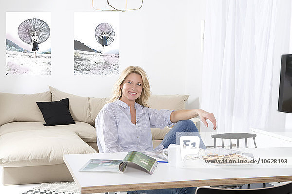Porträt einer lächelnden Frau  die sich am Tisch in ihrem Wohnzimmer entspannt.