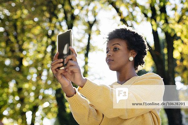 Schöne schwarze Frau mit Smartphone  Outdoor im Herbst