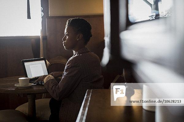 Junge Frau sitzt in einem Café und arbeitet mit einem Laptop.