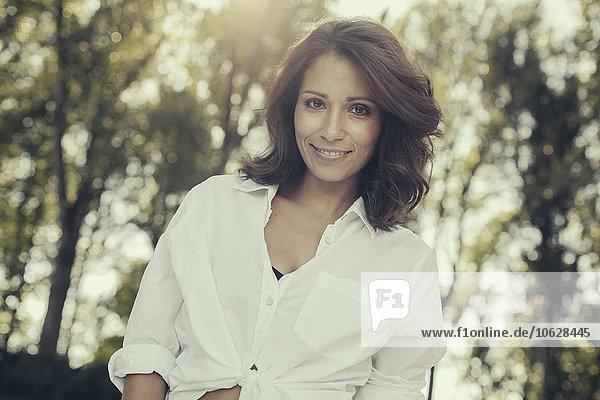 Porträt einer lächelnden Frau mit braunen Haaren in der Natur