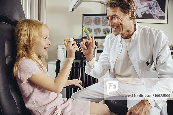 Doctor playing with little girl with in ENT practice  using finger puppets
