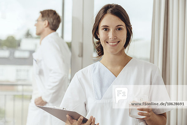 Krankenschwester hält Wasserglas und Klemmbrett  Arzt ruft im Hintergrund an