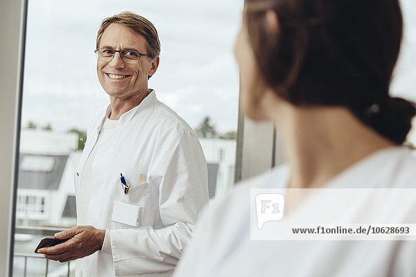 Arzt und Krankenschwester reden im Krankenhauszimmer  lächelnd